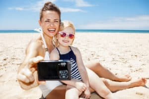 Family fun on white sand. Happy mother and child in swimsuits taking selfies with digital camera at sandy beach on a sunny day ** Note: Shallow depth of field